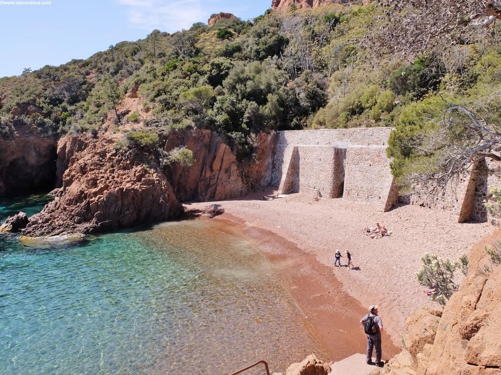 Der Strand St.Barthelemy am Mittelmeer, eingebettet in ockerfarbenen Felsen des Esterel Gebirges